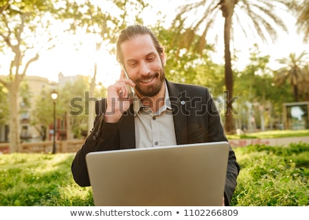 Picture closeup of businesslike handsome man with tied hair work Stock photo © deandrobot