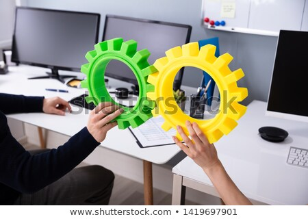 Businesspeople's Hand Joining Green And Yellow Gears Stock photo © AndreyPopov