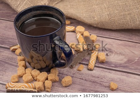cup of coffee sugar cubes and chocolate candy on old wooden background stock photo © melnyk