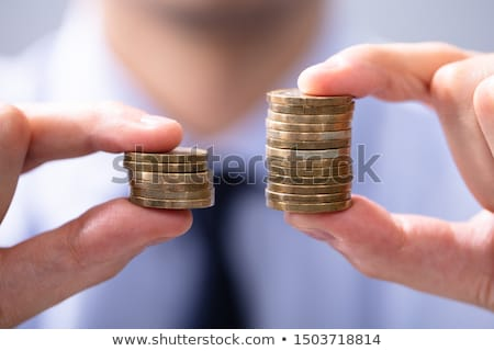 Man Comparing Two Coin Stacks Stock photo © AndreyPopov