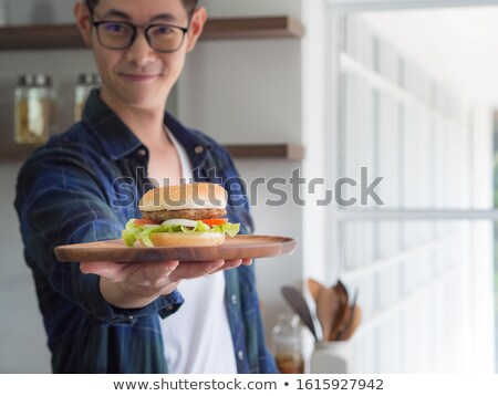 happy young man showing hamburger Stock photo © dolgachov