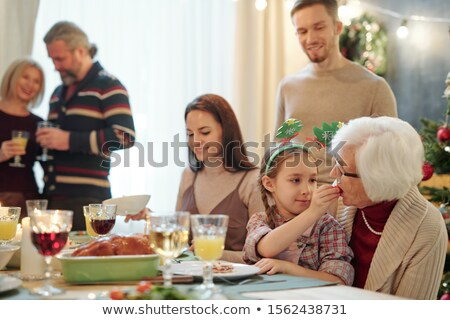 adorable girl giving her great grandmother small tomato by festive table stock photo © pressmaster