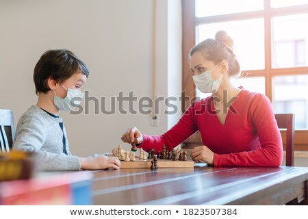 Mother and son playing chess to kill some time during curfew in crises Stock photo © Kzenon