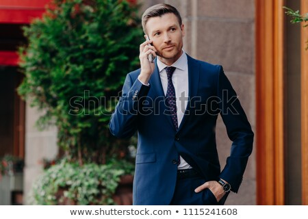 Young male CEO has telephone conversation, looks confidently into distance, dressed in elegant suit, Stock photo © vkstudio