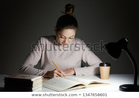 Young female student preparing for exams late at home  Stock photo © Elnur