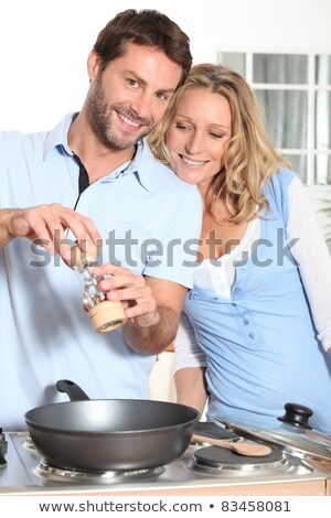 couple using peppper grinder while cooking in the kitchen stock photo © photography33