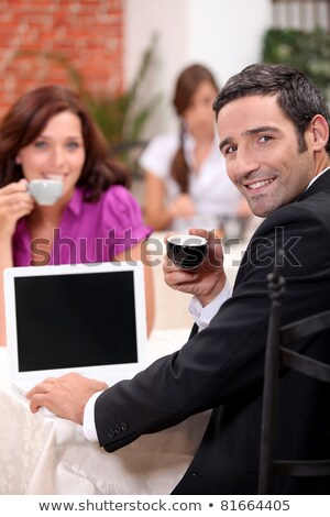 Couple drinking expresso in a cafe with a laptop screen left blank for your image Stock photo © photography33