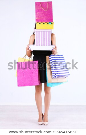 Stock photo: Young woman with a pile of shopping bags