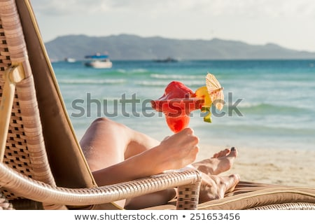 Woman sunbathing and drinking a cocktail on the beach Stock photo © RTimages