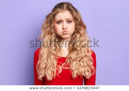 beautiful young lady with blond hair blowing something from her stock photo © elmiko