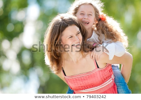 Woman giving her daughter a piggy back ride Stock photo © photography33