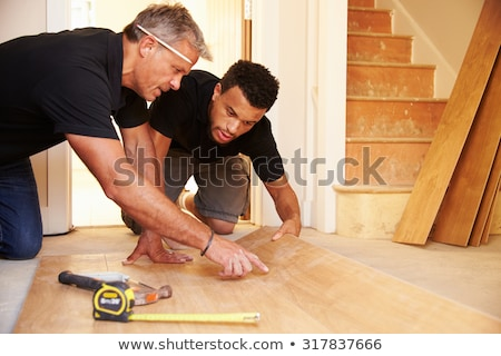 Carpenter and apprentice kneeling Stock photo © photography33
