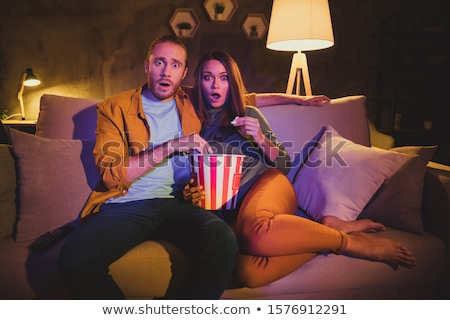 Scared woman watching a horror movie with her boyfriend in the living room Stock photo © wavebreak_media