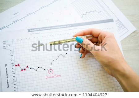 Woman hand holding thermometer on fertility chart Stock photo © simpson33