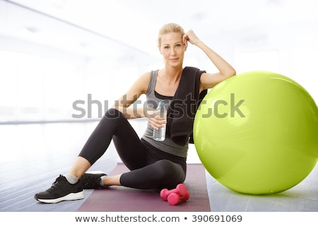 portrait of woman holding water bottle and exercise mat stock photo © wavebreak_media