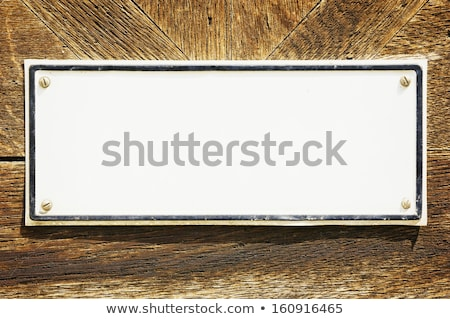 empty metal sign in front of a white wooden wall stock photo © zerbor