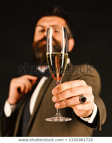 business man holding up a glass of champagne stock photo © feedough