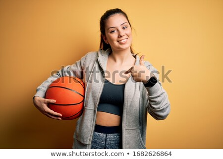 sports woman holding basketball ball stock photo © deandrobot