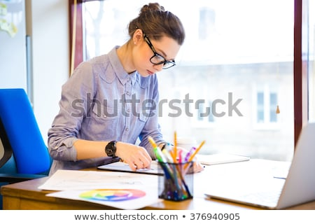 Creative woman fashion designer in glasses sitting and drawing sketches  Stock photo © deandrobot