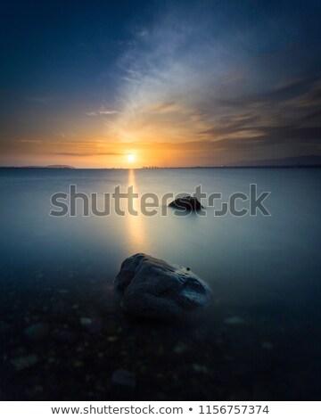 Eau roches coucher du soleil plage Photo stock © clearviewstock