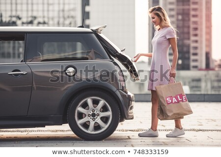 Caucasian woman putting her shopping bags into the car trunk Stock photo © vlad_star