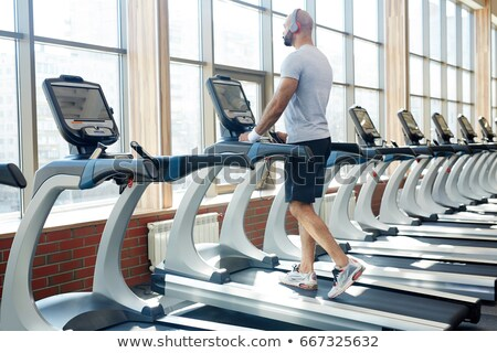 Back view of sportsman working out and running on treadmill Stock photo © deandrobot
