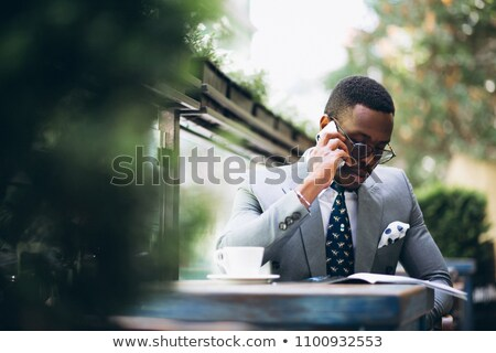 smiling man drinking coffee and reading magazine in outdoor cafe stock photo © deandrobot