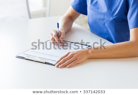 close up of doctor or nurse writing to clipboard stock photo © dolgachov
