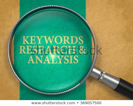 keywords research and analysis through loupe on old paper stock photo © tashatuvango
