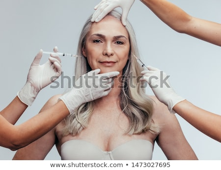 Woman is getting filler injection in cheeks. Anti-aging treatment and face lift. Cosmetic Treatment  Stock photo © flisakd