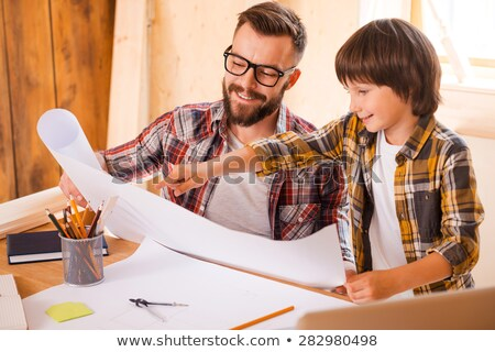 happy father and son with blueprint at workshop stock photo © dolgachov