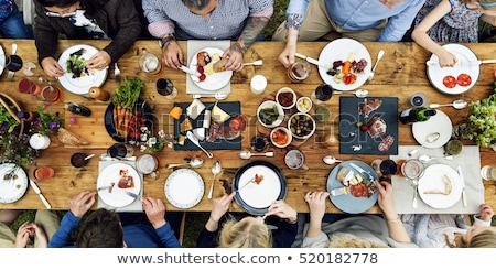 group of people eating at table with food stock photo © dolgachov