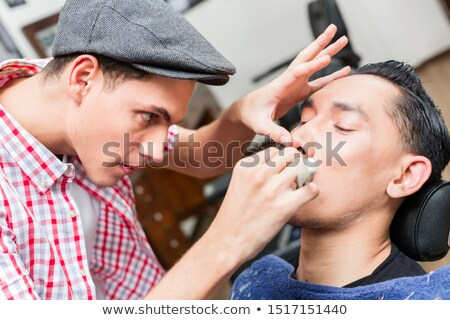 Male barber wearing baseball cap shaving with razor Stock photo © Kzenon