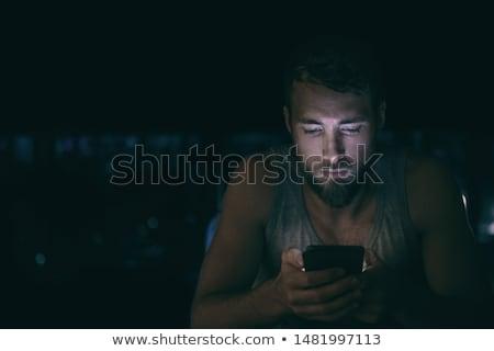 férfi · ágy · okostelefon · mosolyog · fiatalember · visel - stock fotó © lopolo