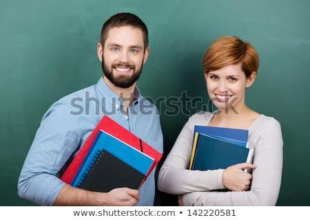 friendly teacher standing in front of blackboard in class stock photo © kzenon