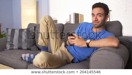 Young attractive mexican man at home sitting on couch Stock photo © Lopolo