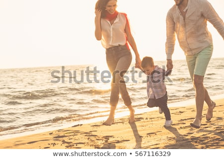 Stock photo: Happy young family have fun on beach run and jump