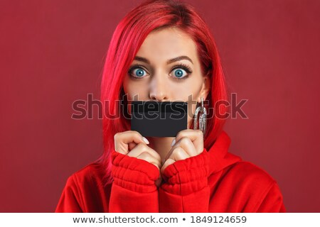 portrait of a cute young woman casually dressed holding a credit card at her face stock photo © ichiosea