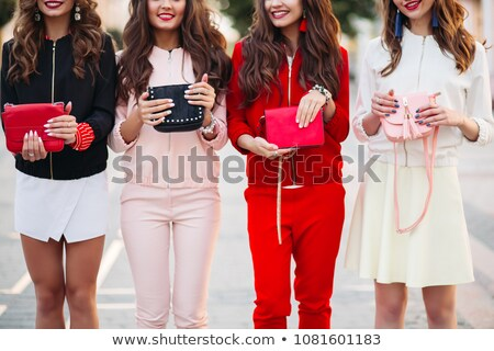 Smiling girlfriends with manicure holding handbags. stock photo © studiolucky