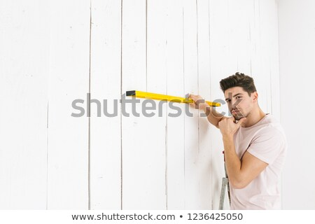 Image of handsome guy 20s holding big ruler at white wall, while Stock photo © deandrobot