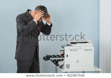 Irritated Businessman Looking At Printer Machine Stock photo © AndreyPopov