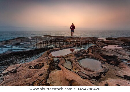 Woman standing on sandstone rocks with foggy coastal sunrise Stock photo © lovleah