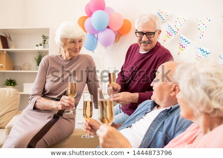 Several aged people with flutes of champagne enjoying home party Stock photo © pressmaster