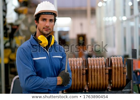 Young factory mechanic or technician working with one of industrial machines Stock photo © pressmaster
