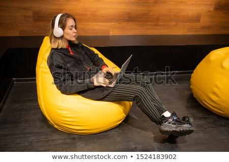 nő · zenét · hallgat · dolgozik · laptop · néz · kamera - stock fotó © pressmaster