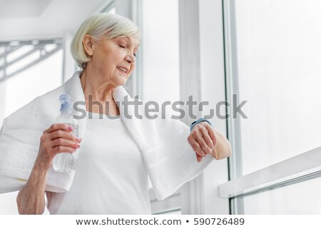 smiling senior woman with fitness tracker Stock photo © dolgachov