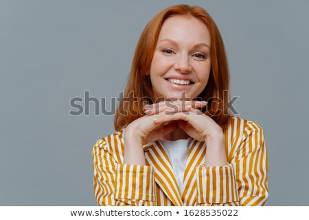 Close up shot of lovely woman has foxy hair, smiles toothily at camera, keeps hands under chin, dres Stock photo © vkstudio