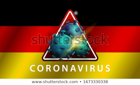 Stock photo: Warning sign with bacteria of Coronavirus on the German flag.