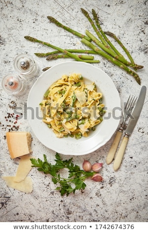 Homemade tagliatelle pasta with ricotta cheese creamy sauce and fresh asparagus served on a iron pan Stock photo © dash