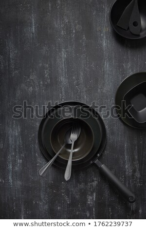 Served kitchen table with black cookware ceramic plates, fork, spoon and textile napkin. Stock photo © artjazz